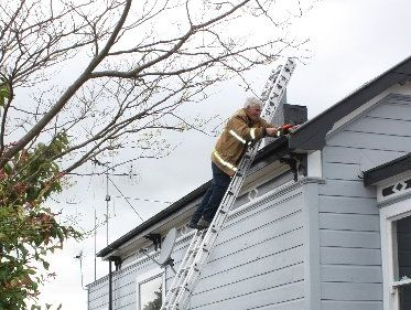 ON A MISSION: Dannevirke volunteer firefighter Andrew Donaldson secures the roof of a home in Swinburn St after high winds began to lift the iron on Sunday morning. PHOTO/CHRISTINE MCKAY DAN12825