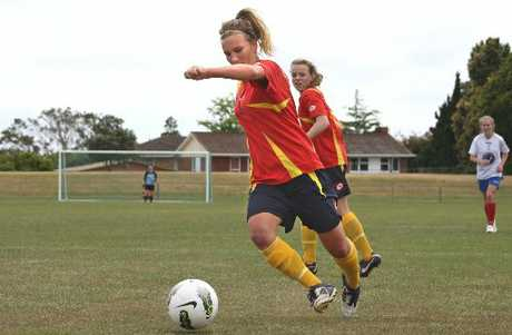 WaiBOP's Kate Carlton on the ball, watched by teammate Issy Coombes.