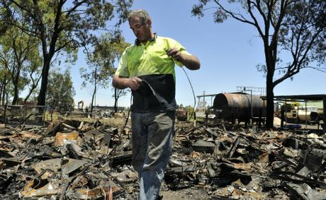 Trevor Hold retrieves copper from the burnt televisions at his Oakey recycling dump.