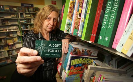 A 2011 photo of the owner of the now-defunct Angus and Robertson book stores at the Sunshine Plaza and Kawana Shoppingworld, Therese Appleby, with a gift voucher.