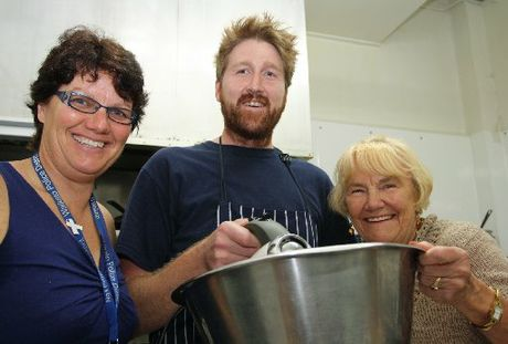 Hazel Hayes' owner-chef Brad Bakker, assisted by swimming sensations Gail (left) and Merle Jonson, mix a chocolate cake for tomorrow's Municipal Pool centenary celebrations.