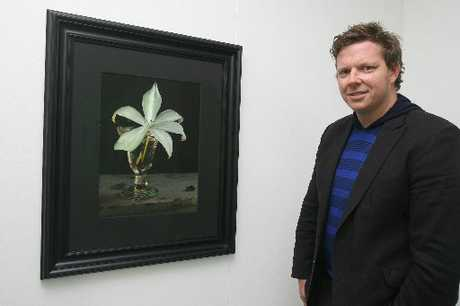 HANGING: Wellington Suite Art Gallery owner David Alsop with one of Fiona Pardington's prints, Still Life with Fragrant Lily and Bumblebee, at HedSpace until January 5.