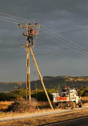 FIERY DAMAGE: Linesmen work after a powerpole exploded and sparked a series of spot grass fires in Te Awanga after yesterday's storm. PHOTO/DUNCAN BROWN HBT124572-03
