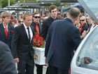 Daniel Morcombe's older brother Dean carries Daniel's white coffin into the hearse as a guard of honour forms around the family.