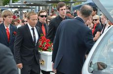 Daniel Morcombe&#39;s older brother Dean carries Daniel&#39;s white coffin into the hearse as a guard of honour forms around the family.