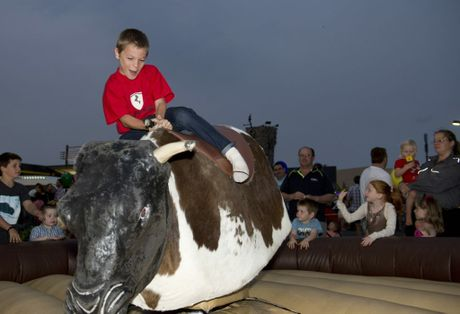 Riley Taylor on the bull ride. Christmas block party at Highfields.