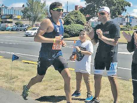Professional triathlete Terenzo Bozzone runs past Ironmaori organiser Heather Skipworth, husband Wayne and son Te Au during the Kelloggs Nutri-Grain Taupo Half-Ironman on Saturday. Photo / Supplied