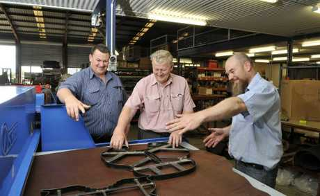 Trying out the new leather cutting press are (from left) Rob and Garth Delbridge along with Cameron Dinnes.