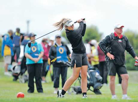 Tessa McDonald tees off with coach Dave Keown looking on at the St Clair club yesterday. Photo / Otago Daily Times