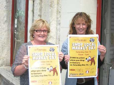 ROLL UP: Kay Parker of Lavish Soaps (left) and Jan Kennedy, Waitaki Tourism event development officer, with posters in readiness for the Oamaru Shop Local Market Day. PHOTO/JACQUIE WEBBY