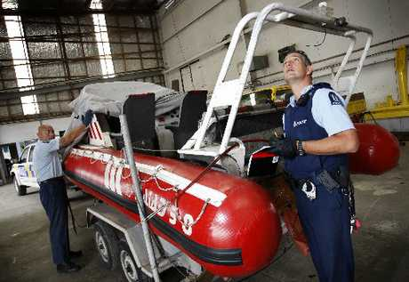 Onerahi community Constables Spence Penney (left) and Aaron Furze examine the boat found dumped on the side of the road. Photo / Michael Cunningham