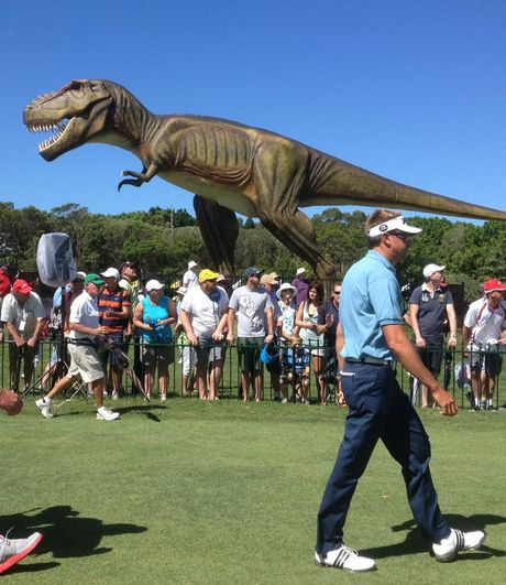 "Robert Allenby walks past Clive Palmer's pet dinosaur ""Jeff"" at the PGA."