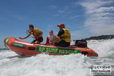 Mount Maunganui lifeguards Robert Sheard (left) and Leigh Sefton escort Santa Claus into the Main Beach for the MMLS Nippers Christmas party.
