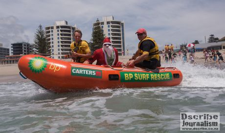 Mount Maunganui lifeguards Robert Sheard (left) and Leigh Sefton bring Santa Claus to the beach.