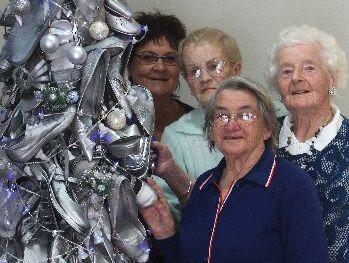 The tree The Gardens' employee June Hamilton (left) made of shoes has become a major talking point. Residents Pat Monk, Val Hamon and Colette Carey admire her work.