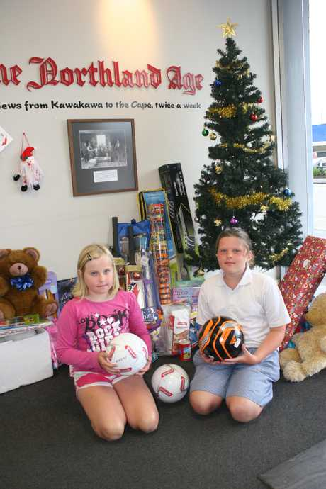 GIFT OF SPORT: Georgia Mellsop and Morgan Doak drop off three footballs donated by NAKFA tournament officials to go under the Christmas tree in the Age office in Kaitaia to be among the gifts intended for underprivileged families. Both girls played for the Mixed Fits team which took part in the family division of the annual 7-a-side social summer soccer championships.