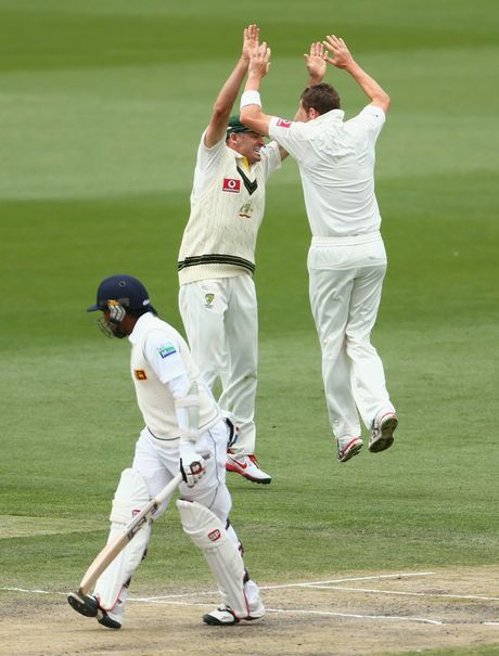 Peter Siddle and Michael Hussey of Australia celebrate the wicket of Mahela Jayawardene of Sri Lanka during day five of the First Test match between Australia and Sri Lanka at Blundstone Arena on December 18 in Hobart.
