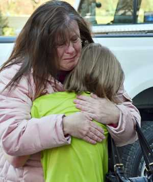 TRAGIC: A mother hugs her daughter during the aftermath of the Sandy Hook Elementary School shooting.