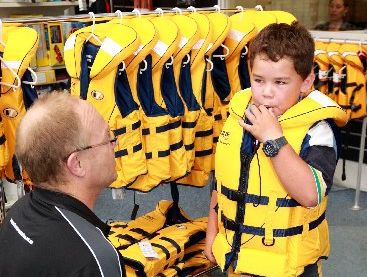 PREPARED: Firmans Marine retail manager Richard Choat runs keen young Wairoa boatie Tristan Smith through the workings on the smart new safety jacket he won.