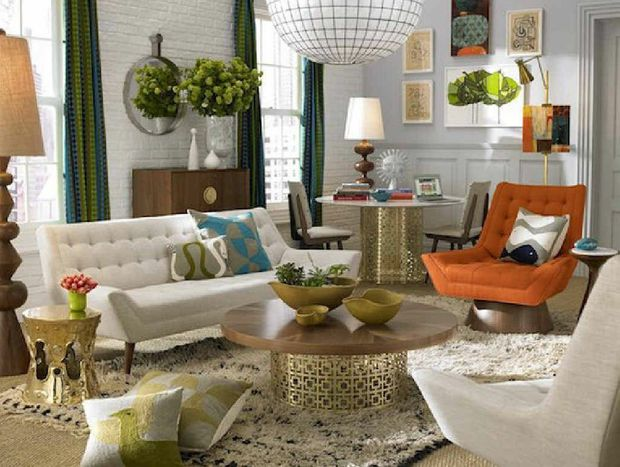 Interior designer Jonathan Adler adds a touch of opulence to this home with gold tables and table lamp.