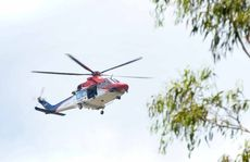 AERIAL HUNT: An emergency services helicopter hovers above bushland in the hunt for Reece Austin yesterday.