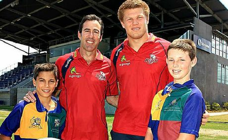 Sunshine Coast Grammar juniors Matthew Henricks, left, and Oliver Osborne, right, rub shoulders with Reds coach Richard Graham, second left, and the Sunshine Coast's Blake Enever at the announcement of the trial game with the Chiefs.