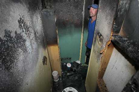 Property owner Bryce Matuschka surveys the damage in the toilet where the fire started. Photo / John Borren