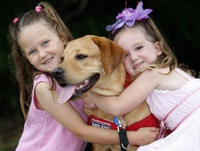 Neve, 7 and Maya Telfar, 5 with their guide dog puppy Vic at the Christmas get-together for the trainers. Photo  / Michael Cunningham