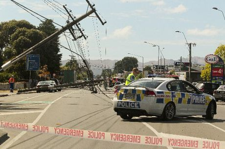 Morning traffic came to a halt when six power poles collapsed across Omahu Rd in an industrial area of Hastings. Photo / Warren Buckland