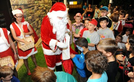 FULL SCHEDULE: Santa keeps himself occupied training his reindeer, overseeing his elves' toy making and appearing at festive functions and events such as this one where he is giving children some treats.