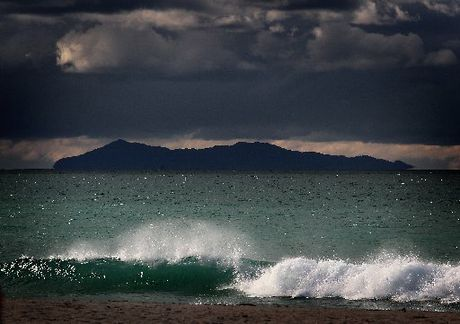 Rain clouds gather over Mayor Island looking across Mount Maunganui's main beach.
