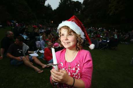 FESTIVE FLAME: Havelock North's Lexxie Cunningham, 7, lights one of the first candles at the Carols by Candlelight at Napier's Botanical Gardens.