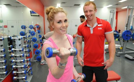 Keegan Lankowski assists Sage Betts with her workout routine at the Jetts Gym in the Westside Shopping Centre.