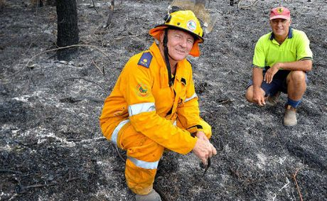 Rural firefighter John MacDonald and property owner Scott MacNicol check the embers.