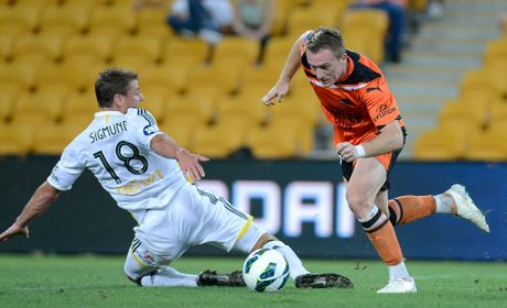 Besart Berisha of the Roar gets around the defence of Ben Sigmund of the Phoenix before kicking a goal during the round 14 A-League match between the Brisbane Roar and the Wellington Phoenix at Suncorp Stadium on January 1, 2013 in Brisbane, Australia.