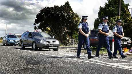 REMEMBERED: Police escorting the remains of the balloon crash victims from the scene at Somerset Rd, Clareville, a year ago.