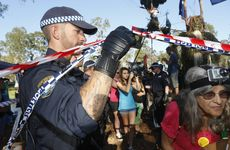 A police officer escorts protestors out of the work site at the Glenugie site. Photo Adam Hourigan / The Daily Examiner