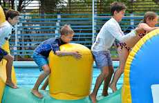 Ryan Franklin (left), Sandon Neilsen, Calvin Franklin and Phoebe Franklin tackle Mission Inflatable at the Pioneer Pool.