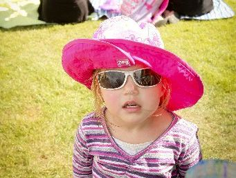 NICE HAT: Zoe Blom, 2, is well protected from the sun as she enjoys a day out with her family at yesterday's concert. HBT130315-9