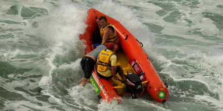 Lifeguards perform a rescue at Mt Maunganui&#39;s main beach yesterday after a large swell built up quickly, catching some surfers unawares.