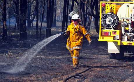 Tinbeerwah Rural Fire brigade member damps down a fire contained on Junction Road Cootharaba. Photo Geoff Potter / Noosa News.