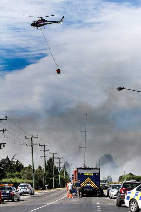 Helicopters with water buckets battle the blaze
