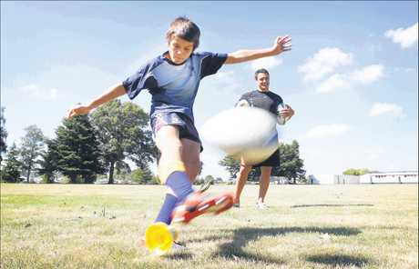 Logan Karauria, 12, kicks the ball as Dan Carter looks on.