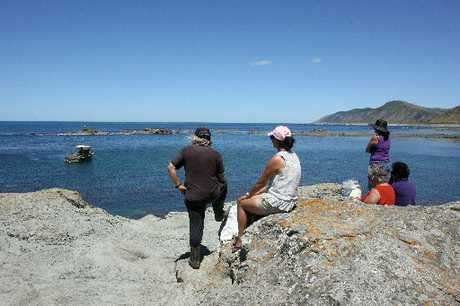 NO NEWS: Family members of missing man Tupara Kiel wait on the shore - his cray pot was set near where the boat is located.