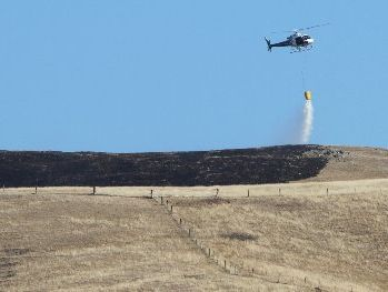 QUENCHED: A helicopter drops water from a monsoon bucket, onto a scrub fire in Poukawa yesterday.