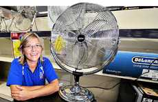 Rebecca Hines from The Good Guys Kawana Waters poses with one of their few remaining fans after a rush to buy them during the heatwave.