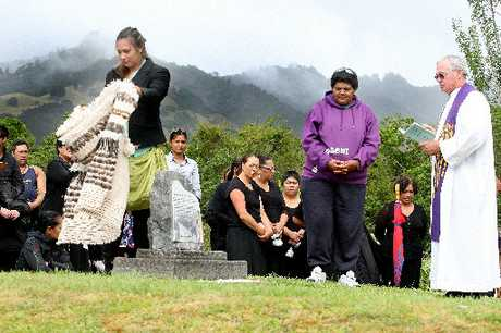 UNVEILED: Aarena Allen removes a cloak from Hohepa Te Umuroa&#39;s gravestone. Waiting to speak is Bubs Mareikura, while Father David Gledhill conducts the service.