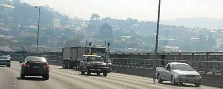 A truck amongst other traffic travels in the smoke haze on the Tasman Bridge.