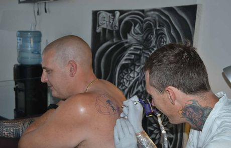 TATTOO ART: Chris Hoye of Smik Tattoo in Woodburn works on some art on Ross Torrance of Woodburn. The charcoal drawing in the background was also done by Chris.