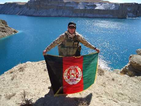 FITTING IN: Trent Morrell hplds up the Afghanistan national flag at Banda Amir lakes.